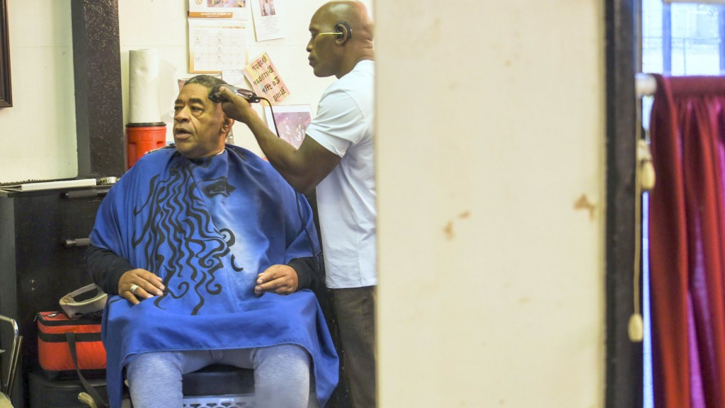 Rev. C.W. Harris talks about the problems needing to be addressed in his Sandtown-Winchester neighborhood while in the barber chair. (J.M. Giordano)