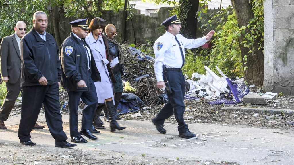 Mayor Catherine Pugh and an entourage of city and police officials tour the Sandtown-Winchester neighborhood. (J.M. Giordano)