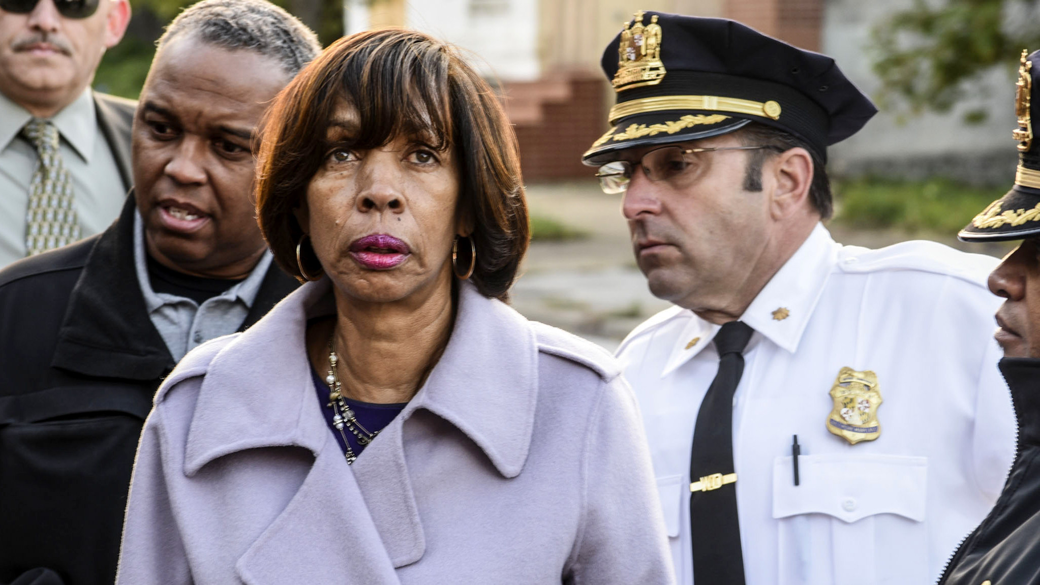 Mayor Catherine Pugh and an entourage of city and police officials tour the Sandtown-Winchester neighborhood. At left, Acting Commissioner Gary Tuggle. At right, Major John Webb. (J.M. Giordano)