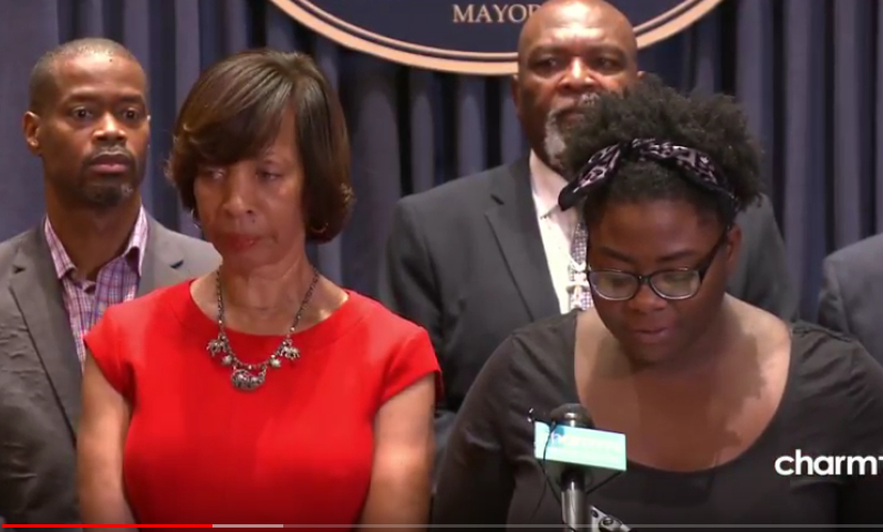 Destiny Watford, of the Baltimore Housing Roundtable, praises Mayor Pugh for signing the MOU for an Affordable Housing Trust Fund at a press conference last month. Behind the mayor is Councilman Leon Pinkett and Minister Glenn Smith. (Charm TV)