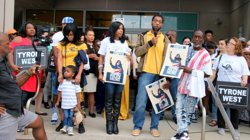 Ray Kelly, of the No Boundaries Coalition, addresses the crowd in front of Baltimore police headquarters. (Fern Shen)