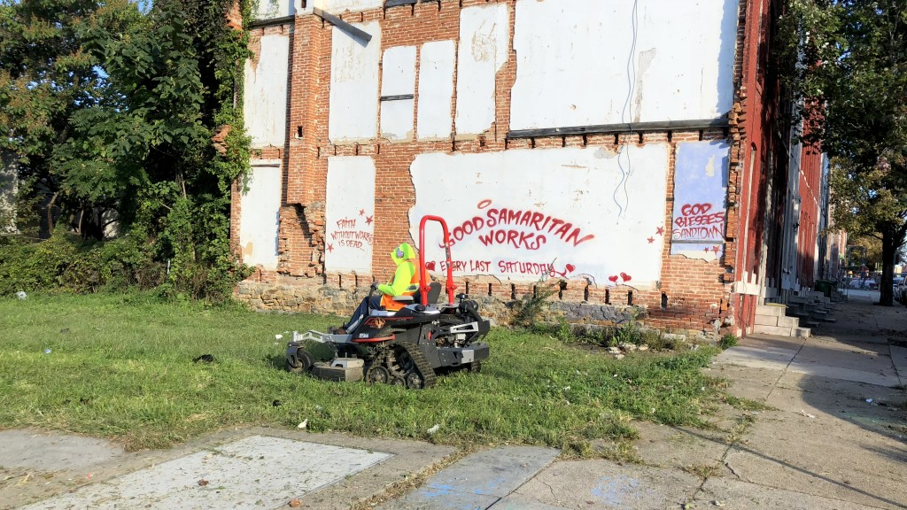 Workers clean up a vacant lot in Sandtown, after a visit by Mayor Catherine Pugh. (Fern Shen)
