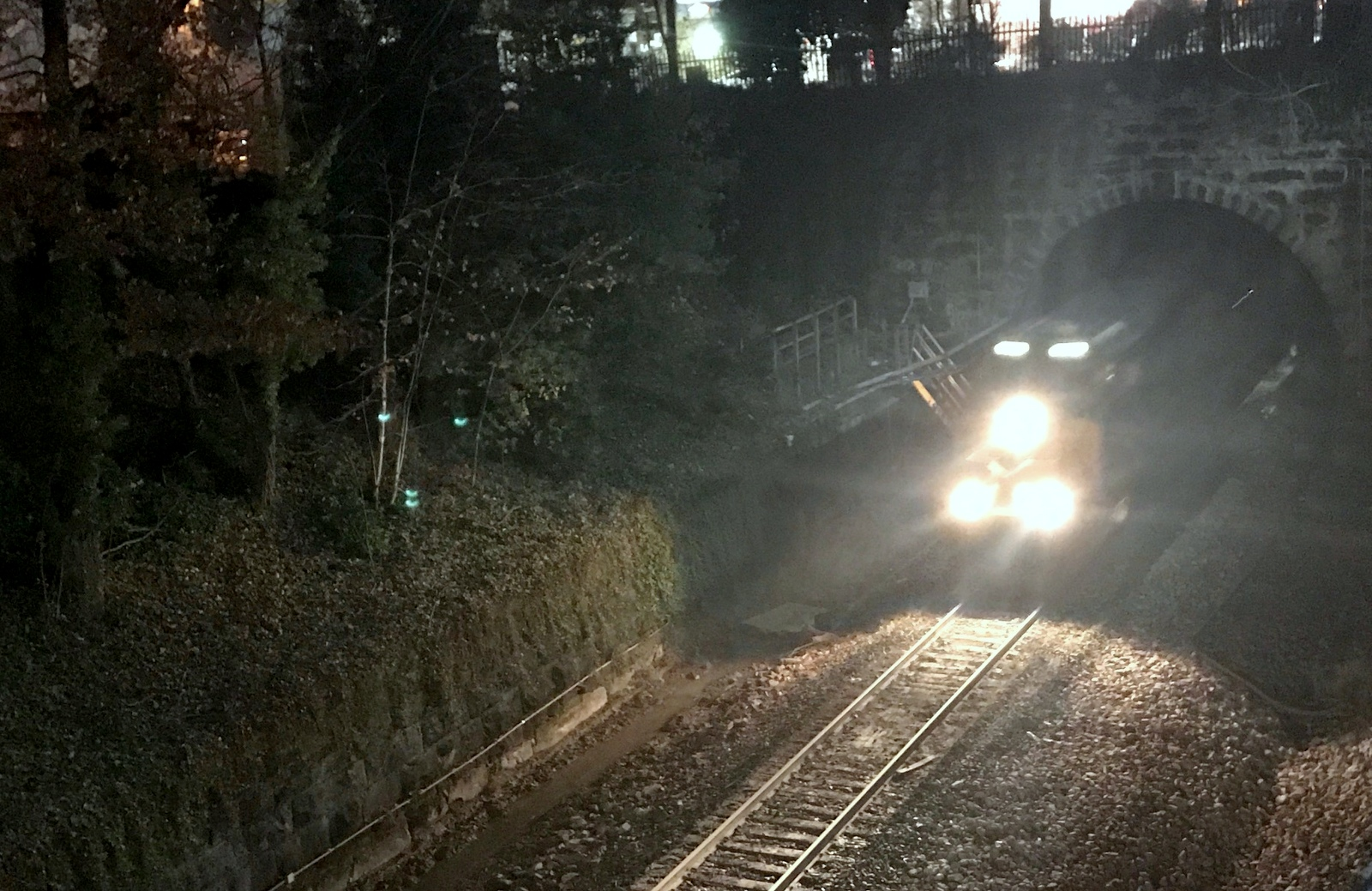 A CSX freight train charges through the cut near Margaret Brent School last night. The freight line was quickly reopened by CSX after emergency excavation had stabilized the wall. (Mark Reutter)