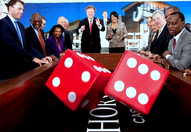 Ex-Mayor Stephanie Rawlings-Blake rolls a pair of oversized dice with former Caesars Entertainment CEO Gary Loveman in a photo op before the casino's opening in 2014. (Brew file photo)