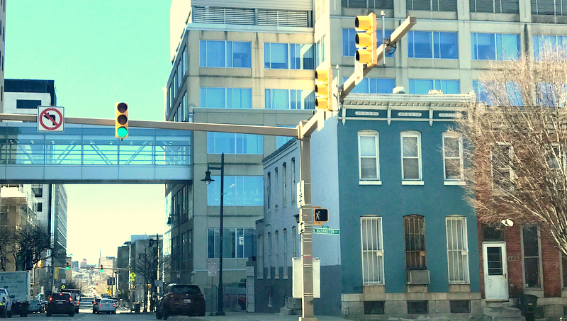 A part of the Johns Hopkins Medical complex rises above rowhouses on Washington Street. (Mark Reutter)