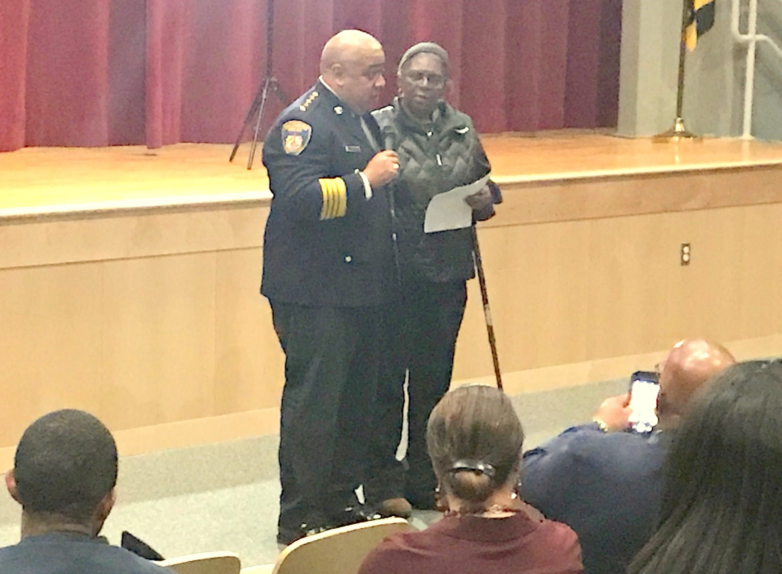 Acting Commissioner Harrison with community activist Kim Trueheart, who gave him a big hug before the audience. (Chase Hoffberger)