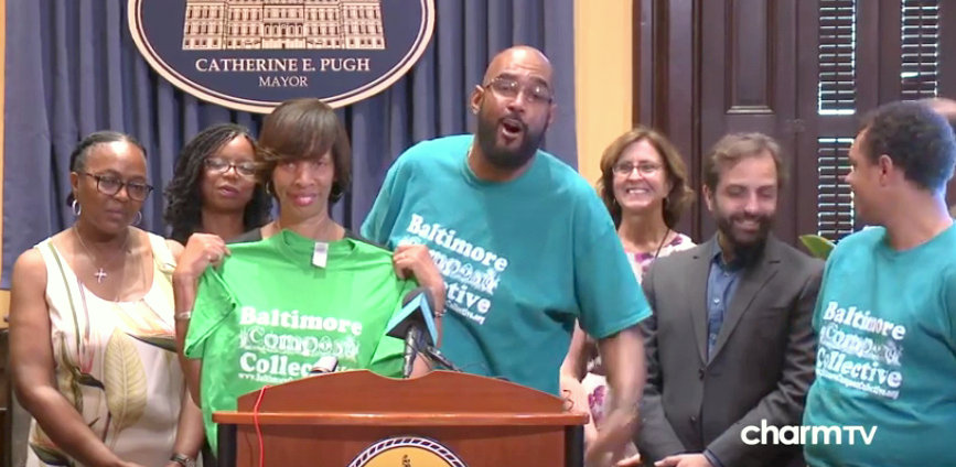 Mayor Pugh accepts a Composting Collective t-shirt presented by program manager Marvin Hayes at a press conference last September. The t-shirt was designed by 19-year-old composter Anthony Walton, seen on the far right. (YouTube)