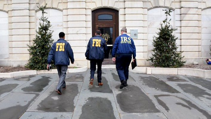 Conducting an early morning raid, agent of the IRS and FBI enter Baltimore City Hall. (J.M. Giordano)