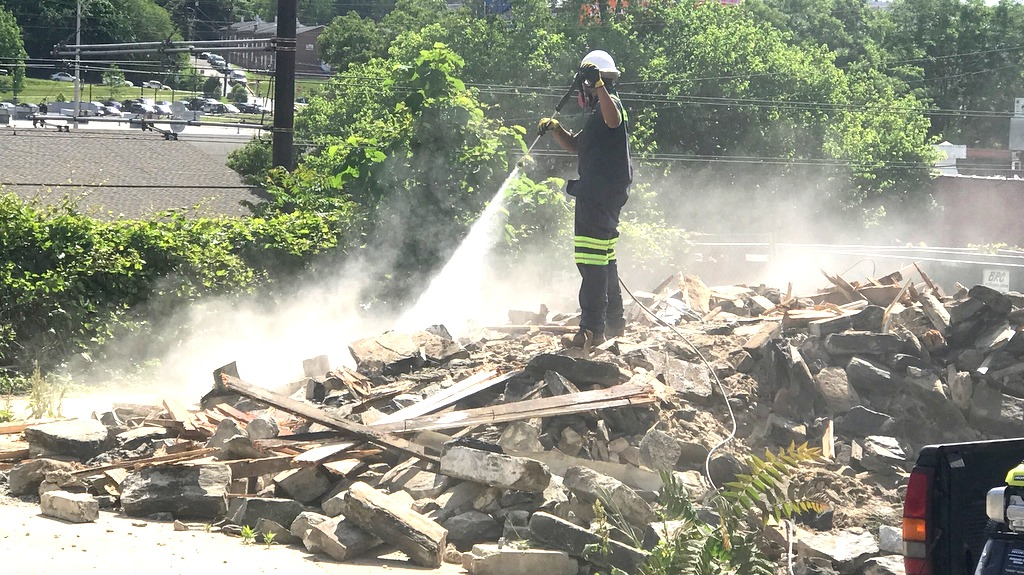 Hosing down the dust from yesterday's Clipper Road demolition. The city says the contractor used insufficient water flow to contain the dust. (Mark Reutter)