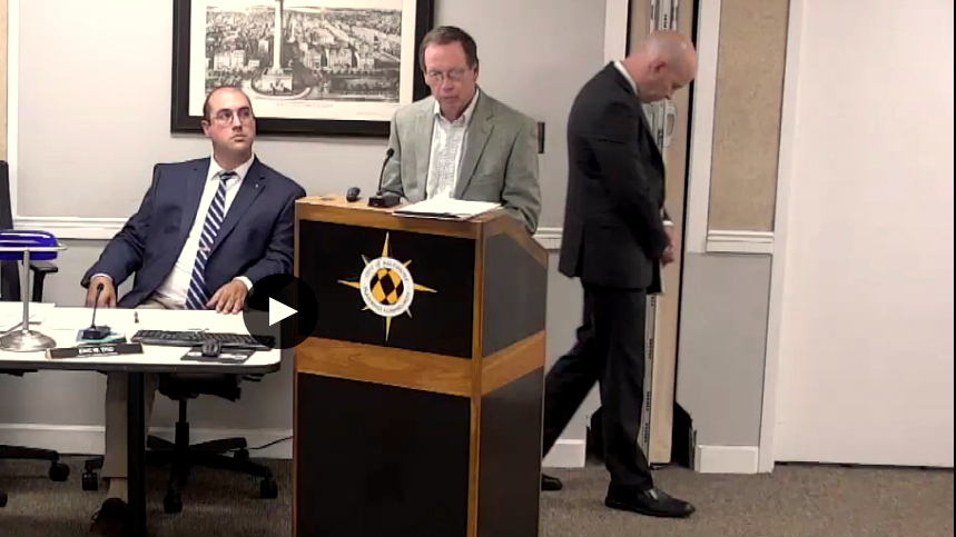 Mercy consultant Al Barry speaks to the Planning Commission yesterday, while the school's attorney, Ryan Potter, walks away from the podium. At left is Planning Department staffer Eric Tiso. (Livestream)