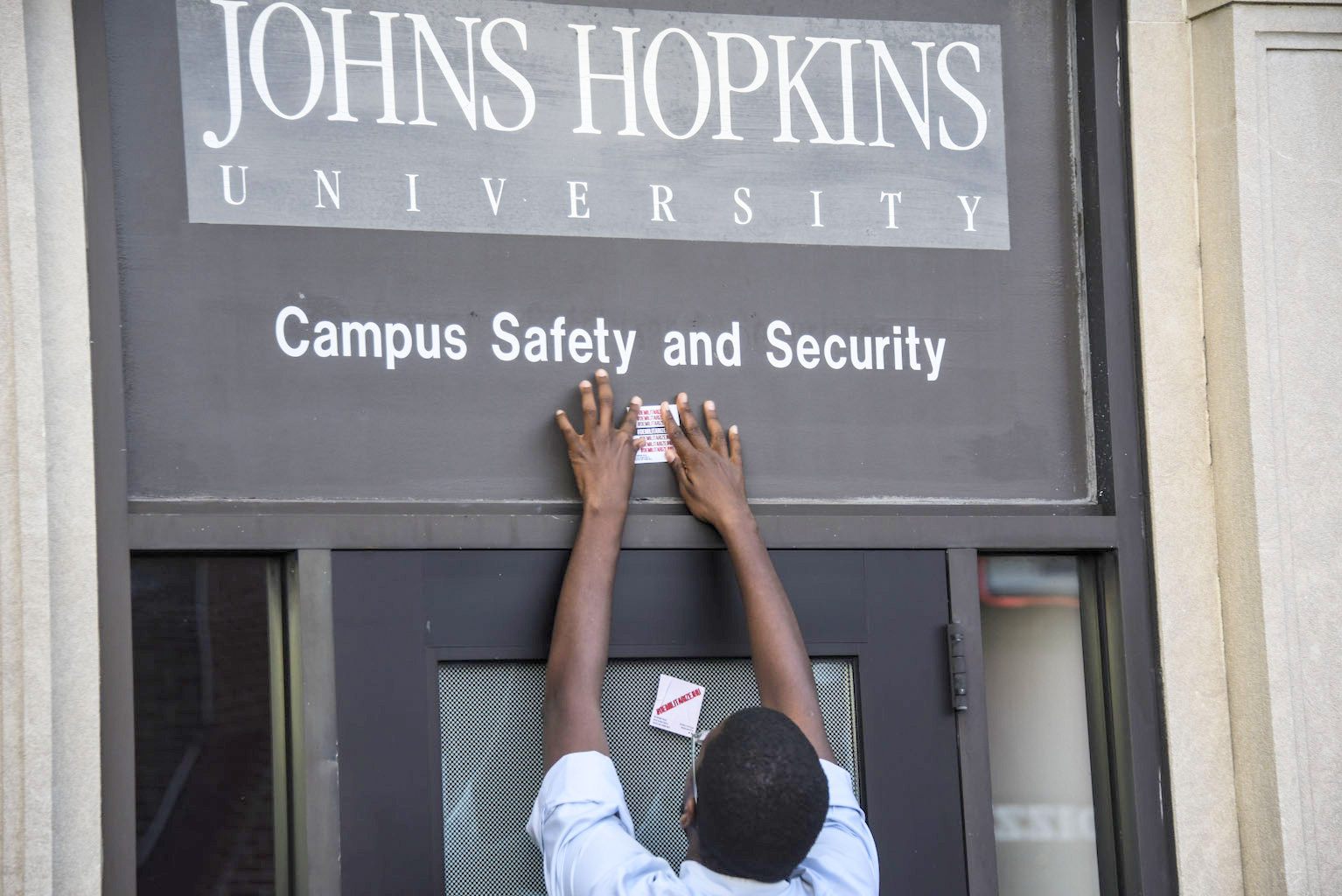 An activist places protest sticker above the door of Hopkins security.