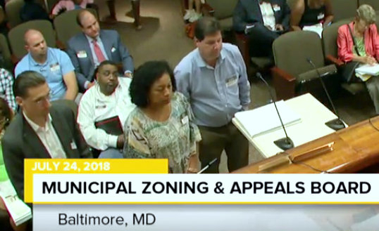 Katherine Jennings does not appear at community meetings or speak to the media. Last July, she appeared at (but did not speak to) the zoning board. Her spokesperson was Michael Burton to her left. (Charm TV)