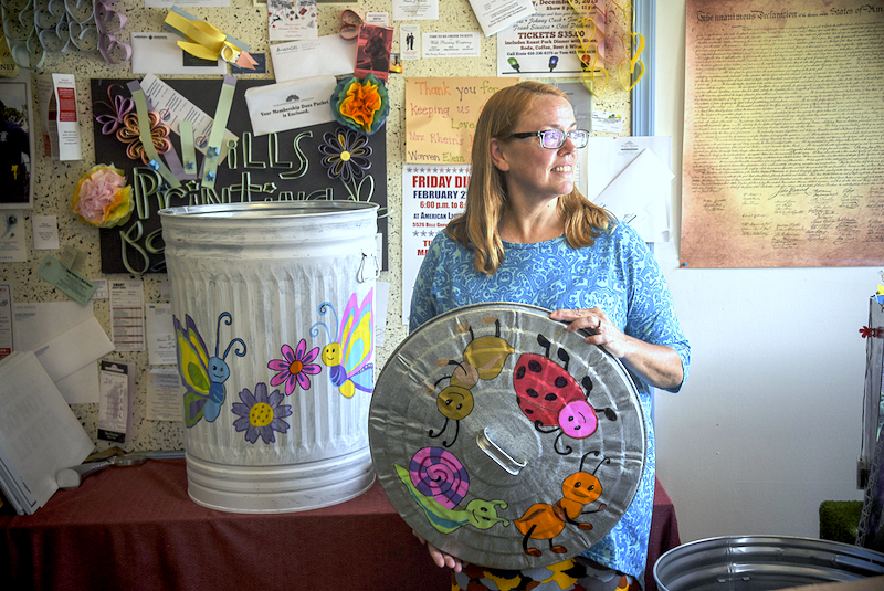 Andrea Mayer in her print shop in Brooklyn with one of the community's new painted trash cans created to encoruage clean streets. (J.M. Giordano)