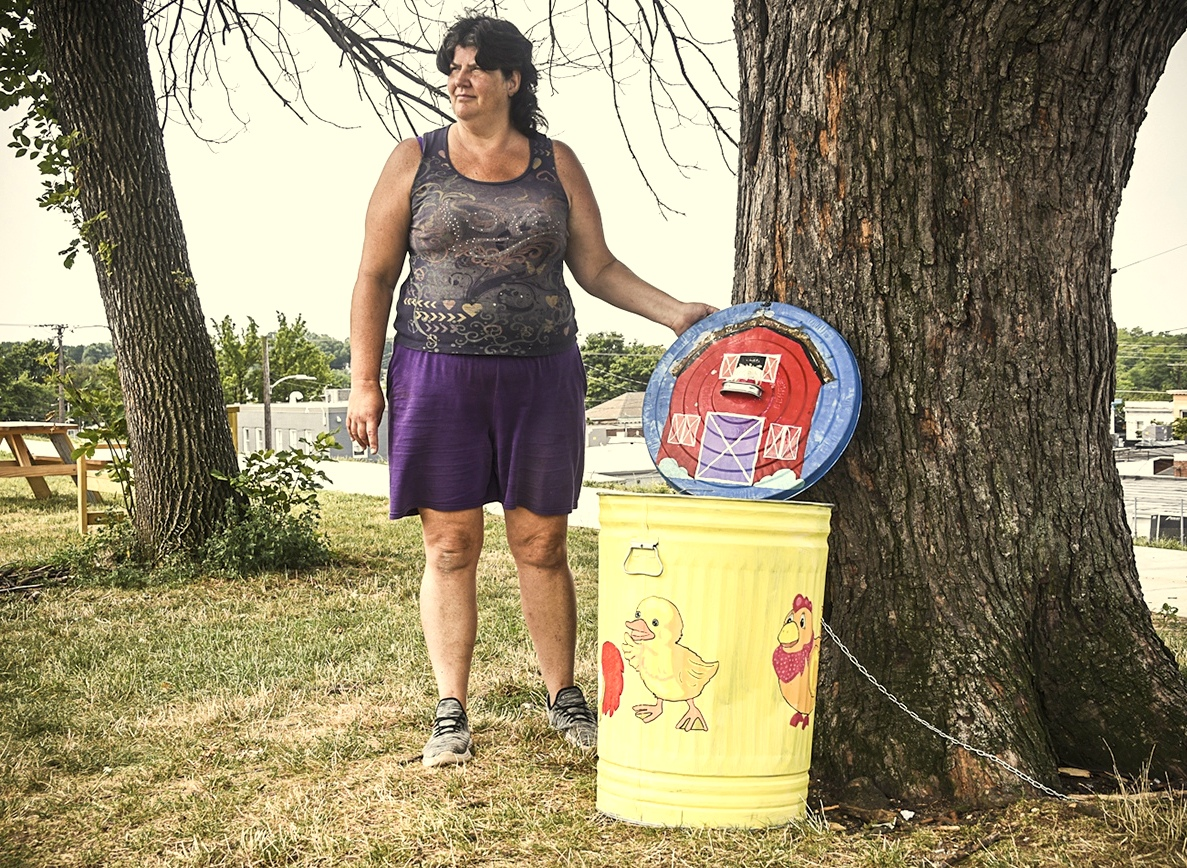 Jamie Gange with one of the painted trash cans in Garrett Park. (J.M. Giordano)