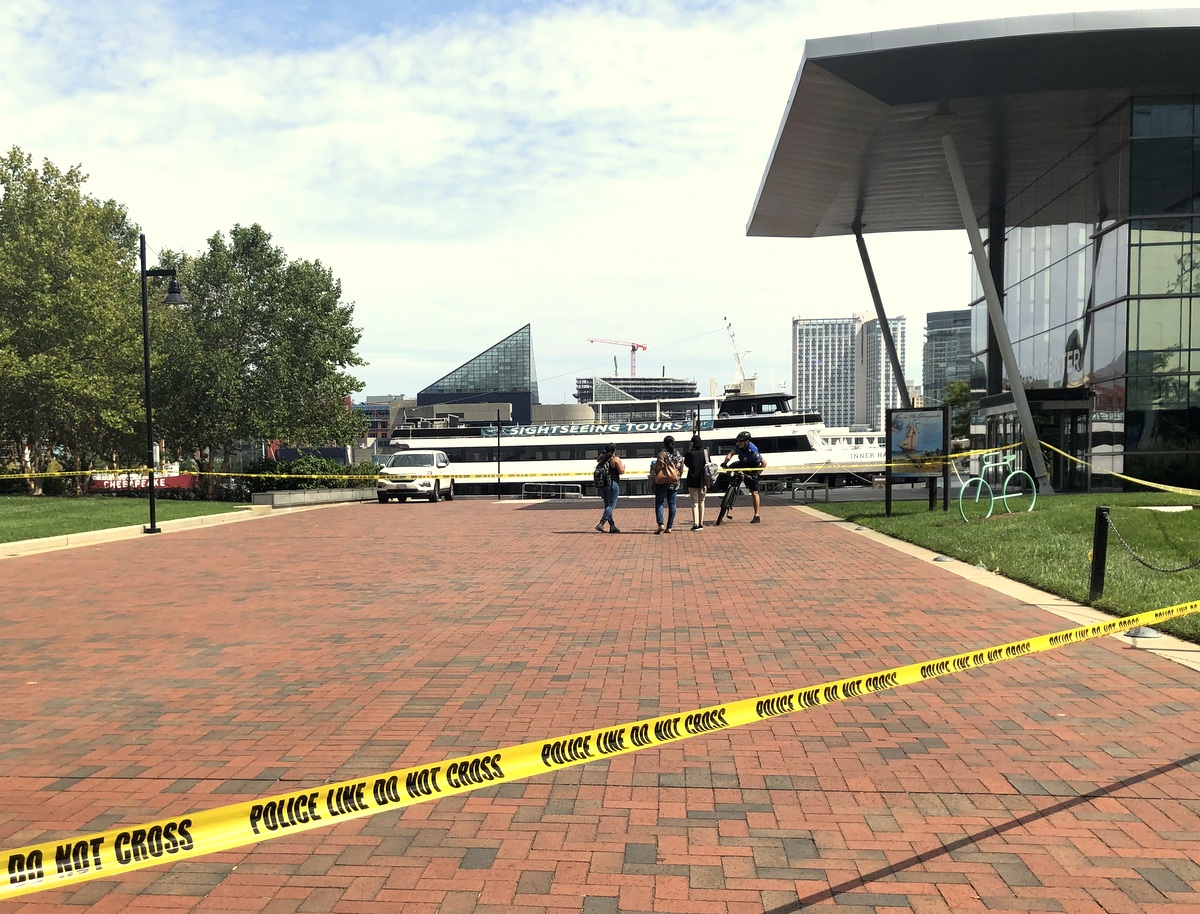 Teenagers ignore the cordoned-off entrance to West Shore Park and head for the Inner Harbor this afternoon.