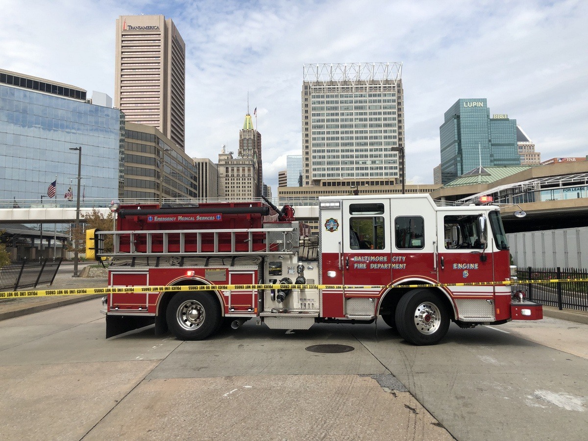 A firetruck at Conway Street blocks off northbound Light Street as police order the evacuation of the three squared-off skyscrapers in the background – 100 Light Street (Transamerica building), 100 East Pratt Street (T. Rowe Price building) and 200 East Pratt Street (with Lupin signage). Photo by Fern Shen.