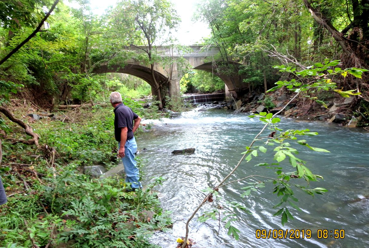An MDE inspector observes the grey chlorinated water rushing into Dead Run from the broken city pipe under the Ingleside Avenue Bridge. (Maryland Department of the Environment)