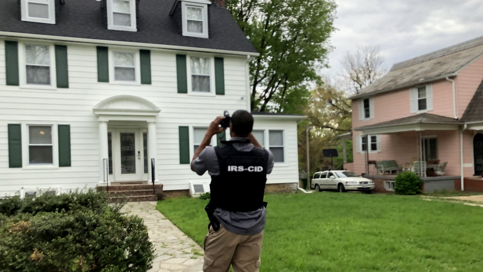 IRS agent photographing Pugh's Ellamont Road house. (Fern Shen)