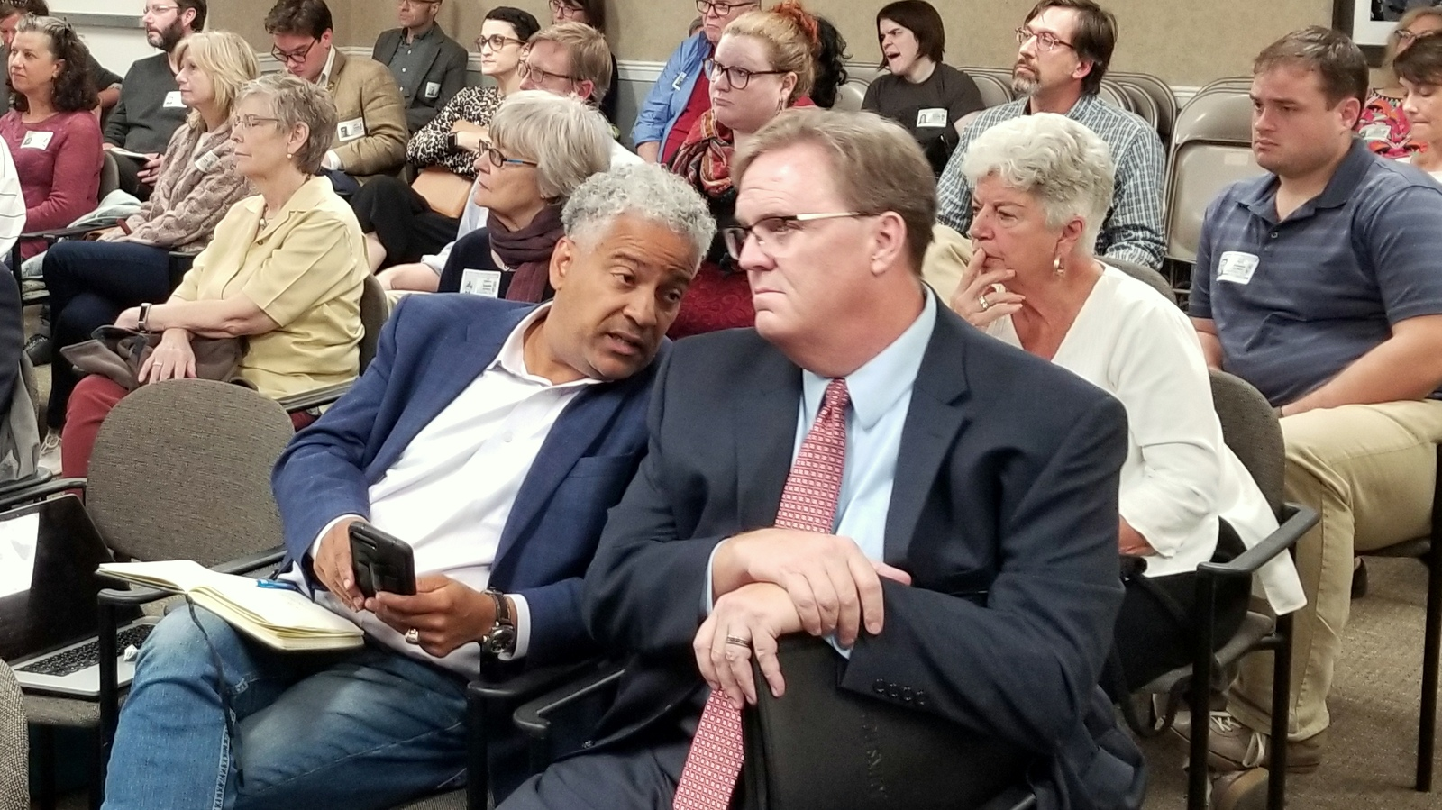Larry Jennings (holding cellphone) confers with co-developer Marty Cadogan, the mayor's campaign treasurer, during November's Planning Commission meeting about their controversial Clipper Mill project. (Ed Gunts)