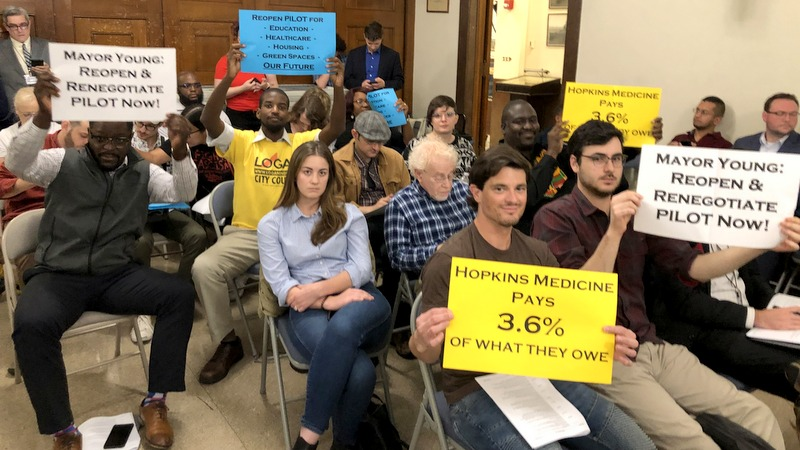 Demonstrators at an October City Council meeting call for renegotiation of the PILOT agreement with non-profits. (Fern Shen)