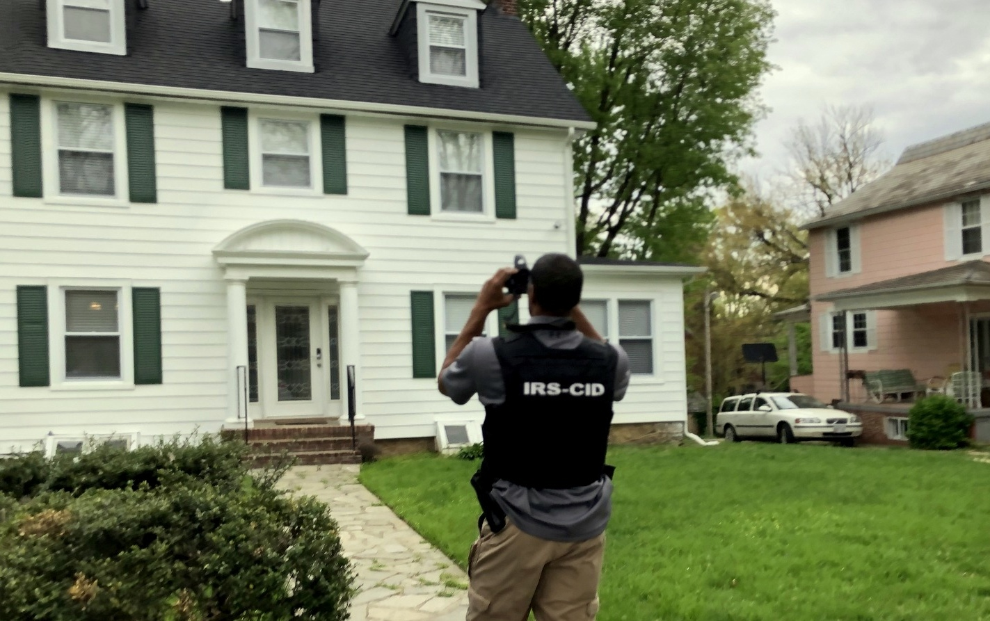 An IRS agent photographs last April Pugh's Ellamont Road house that was purchased with the help of a $100,000 check signed by J.P. Grant. (Fern Shen)
