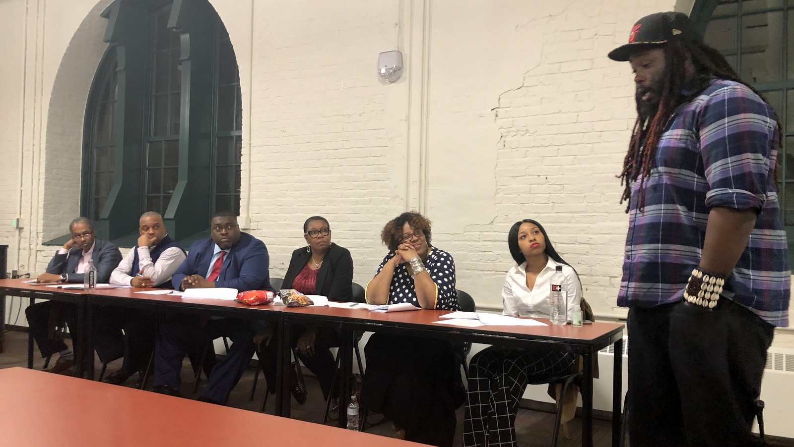 Candidates, including David Fakunle (right), faced six central committee members. Committee chair Branch, herself a candidate, did not sit with the others. (Fern Shen)