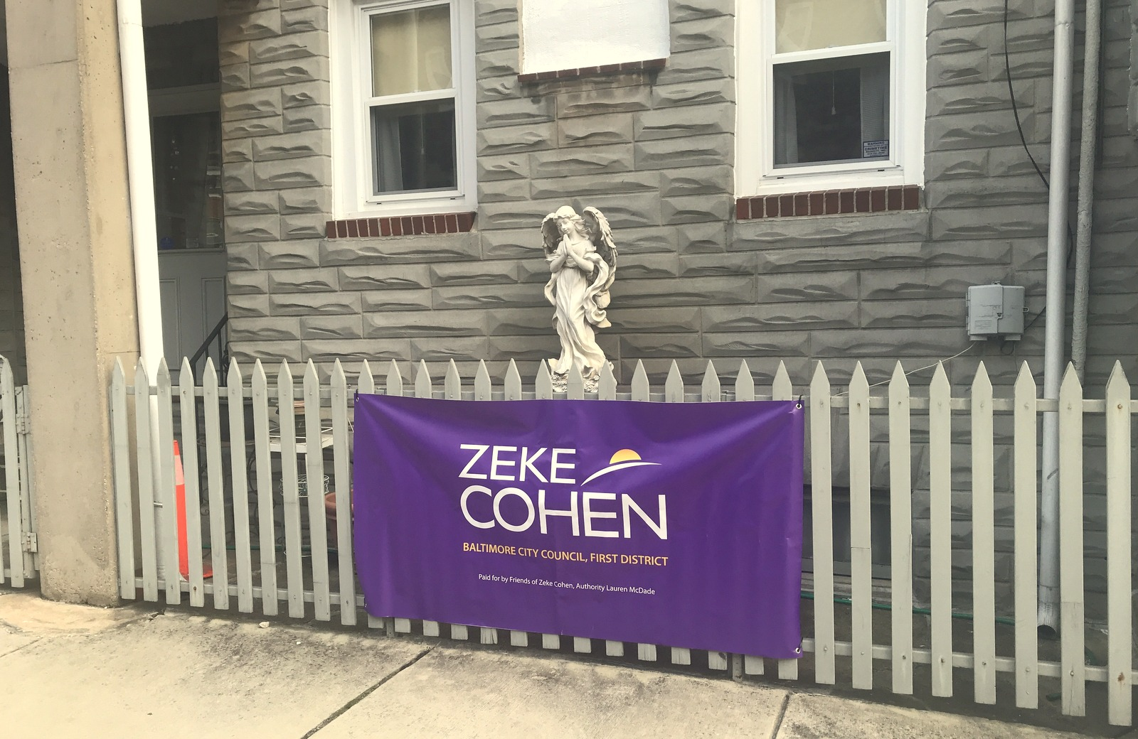 A plaster angel shares space with a Cohen campaign banner in Little Italy. (Mark Reutter)