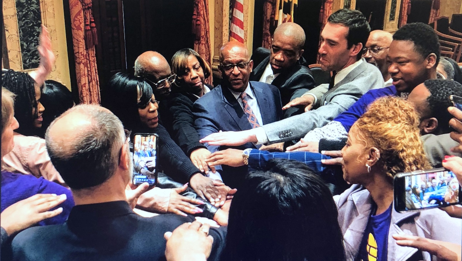 At a March 11 press event, Mayor Young, Councilman Zeke Cohen and others touch hands to celebrate the launch of the Trauma Informed Care Task Force. (@mayorbcyoung)