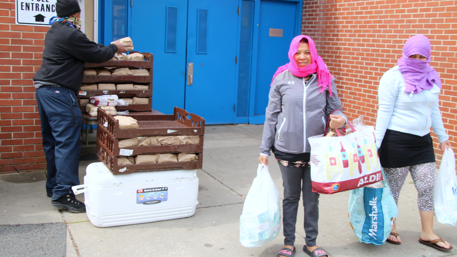 Doris George (left) and Jeraldin Garcia (right) pick up food at Liberty Rec and Tech Center in Northwest Baltimore. (Louis Krauss)