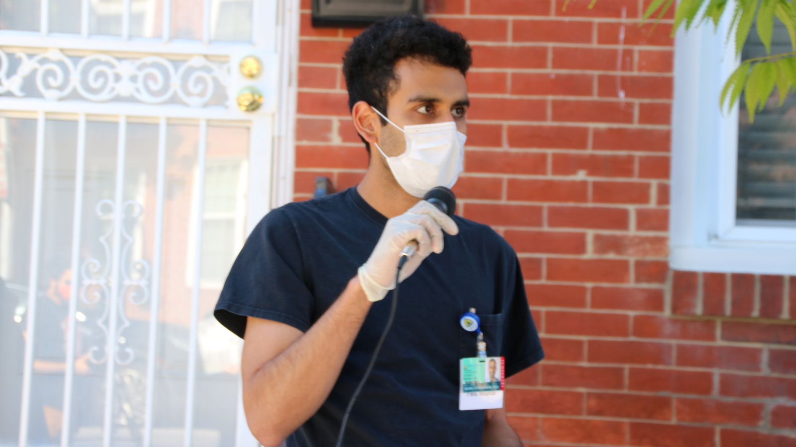 Mihir Chaudhary, a Johns Hopkins physician, addresses the crowd outside Jack Young's house. (Louis Krauss)