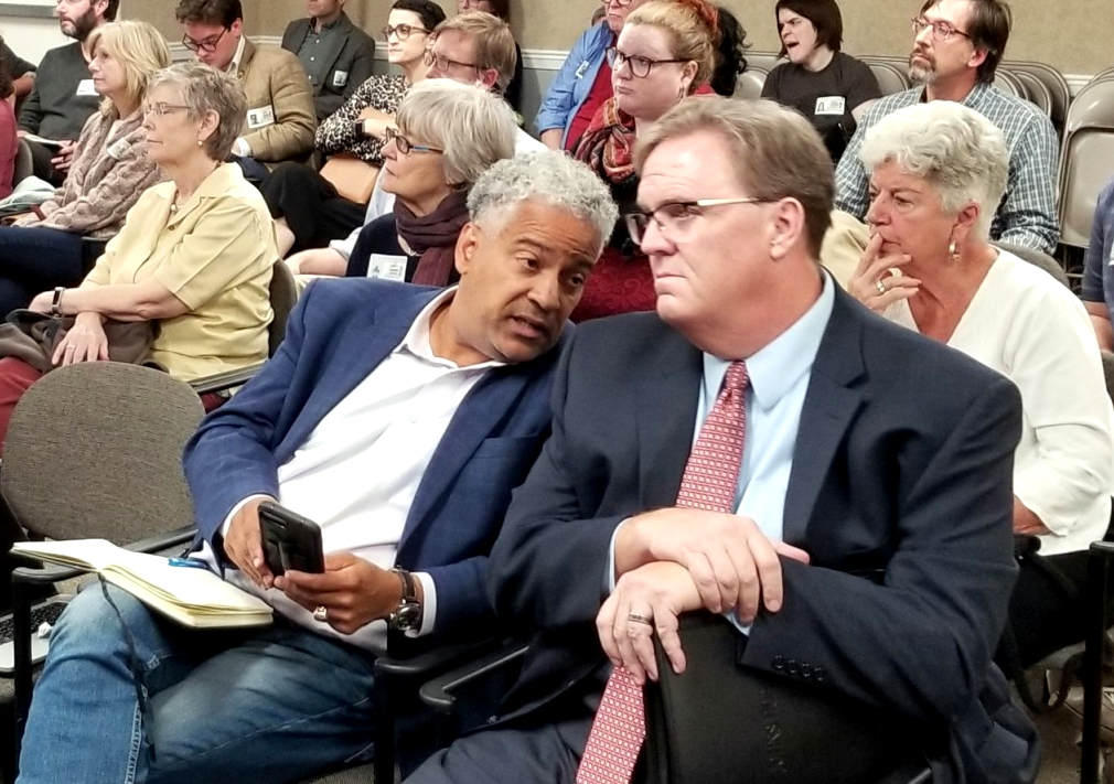 Developer Larry Jennings (holding cellphone) confers with Marty Cardogan, Mayor Jack Young's campaign treasurer, during last November's Planning Commission meeting. (Ed Gunts)