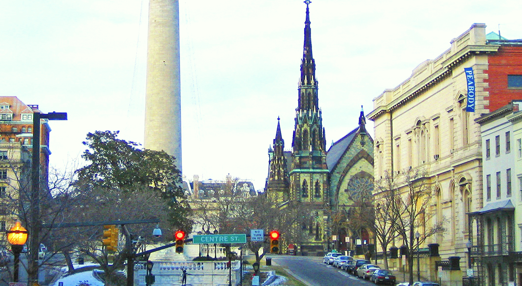 The distinctive green-toned church on Mount Vernon Place is seen between the white marble shaft of the Washington Monument and Peabody Institute, the oldest music conservatory in the U.S. (Wikimedia Commons)