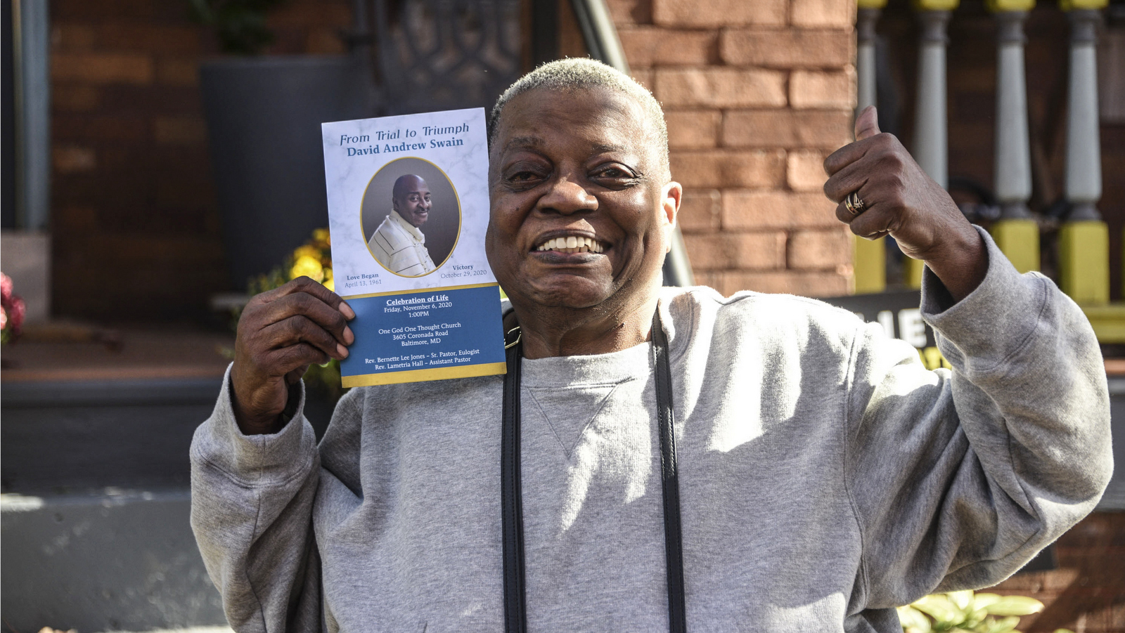 In Baltimore's Charles Village, holds up a photo of her late brother David Swain, who voted for Joe Biden the day before he died. (J.M. Giordano)