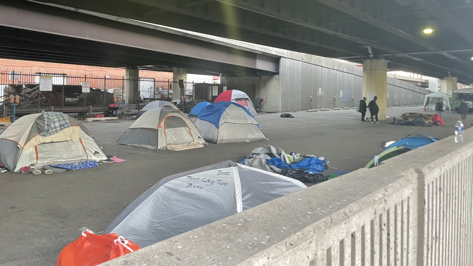 An encampment of people living on a city-owned parking lot under the Jones Falls Expressway that Mayor Jack Young had planned to raze. (Louis Krauss)