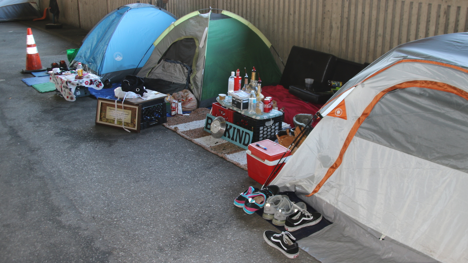 Outside a cluster of tents along Baltimore's Guilford Avenue, makeshift tables hold snacks, toiletries, bottles of soda and juice and in one case a mini-bar. (Louis Krauss)