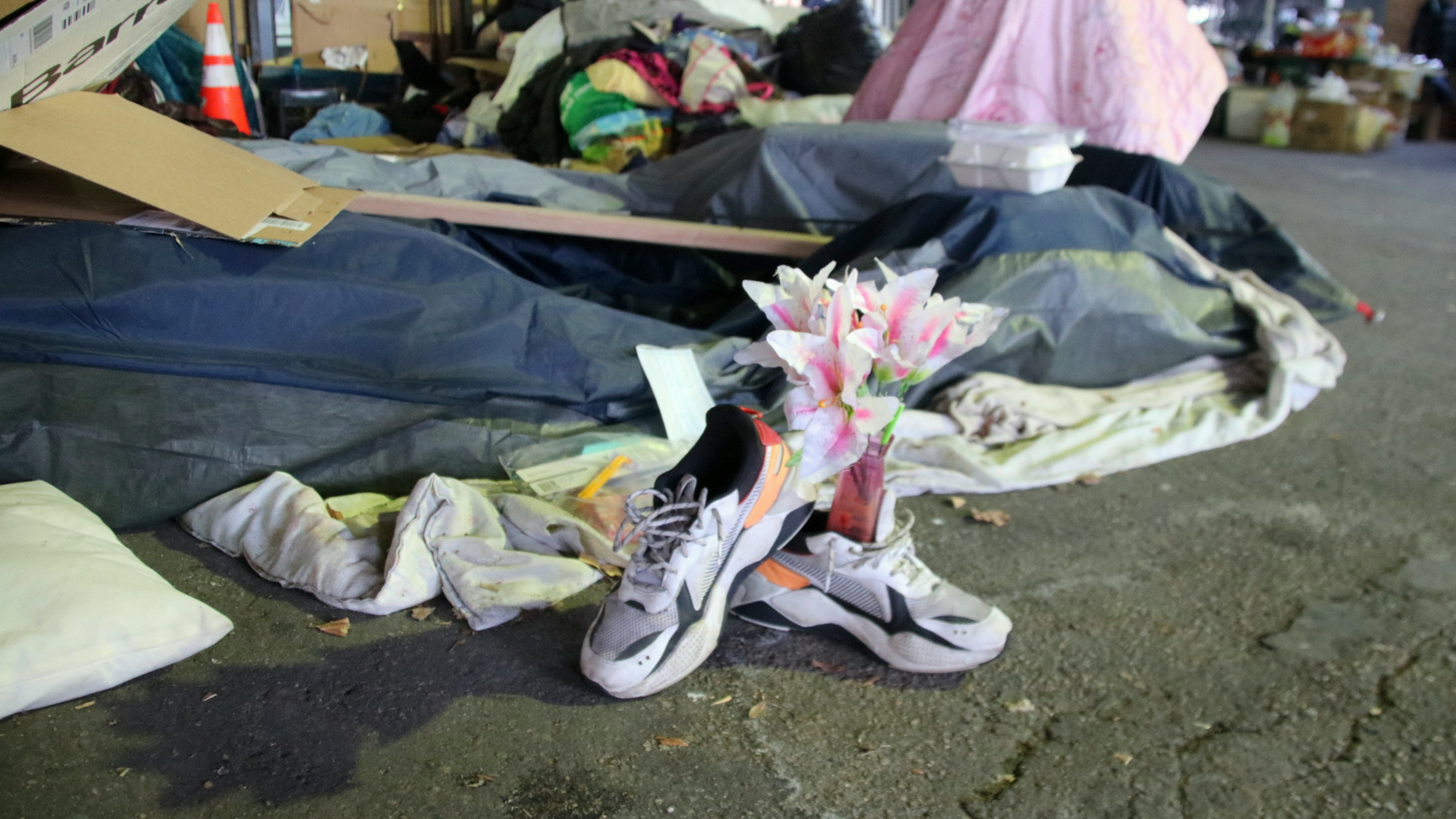 A makeshift memorial for Sherry Woods, who died Thursday in the now-collapsed blue tent behind this pair of her old shoes. (Louis Krauss)