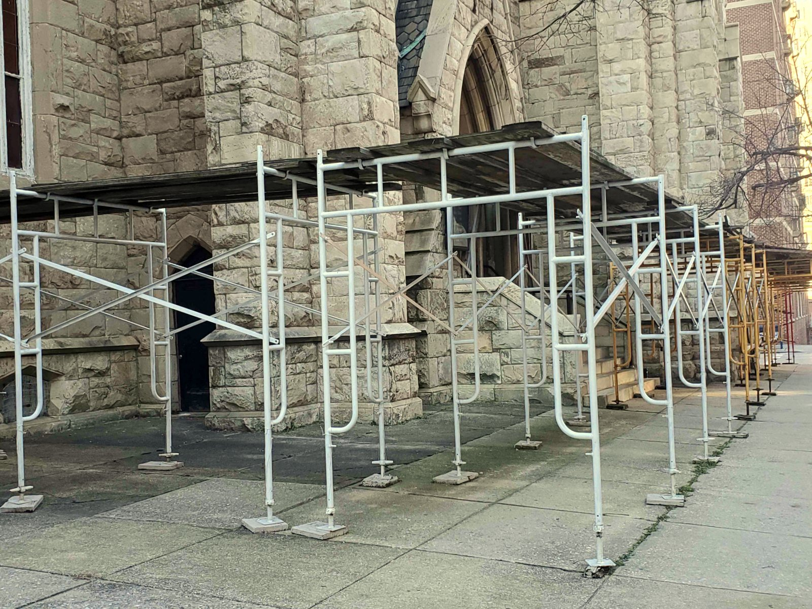 The scaffolding has protected pedestrians from falling tiles and other debris for nearly a decade. (Ed Gtuns)