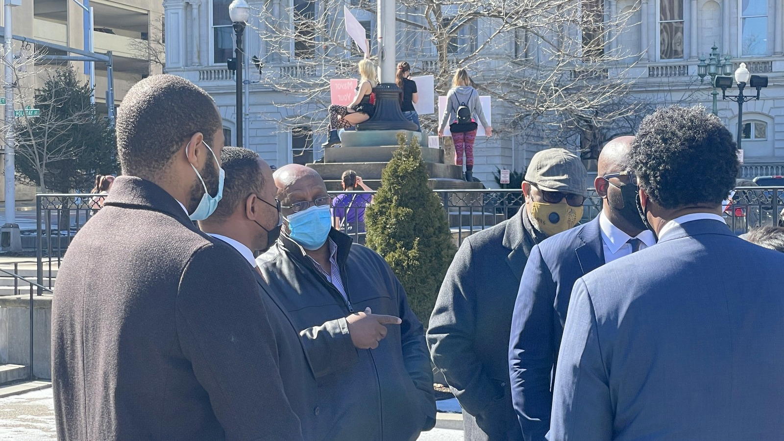 Former mayor Jack Young (in blue mask) with others who had planned to raise questions about Inspector General Isabel Cumming's report on Marilyn Mosby but held off when they discovered a group of strip club dancers were holding a protest nearby. (Louis Krauss)
