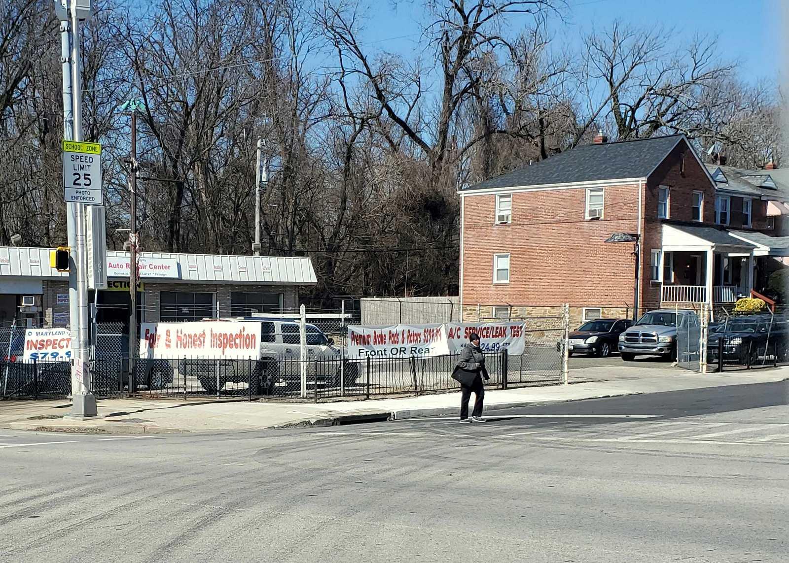 A pedestrian crosses Tioga Parkway next to the auto shop. (Ed Gunts)