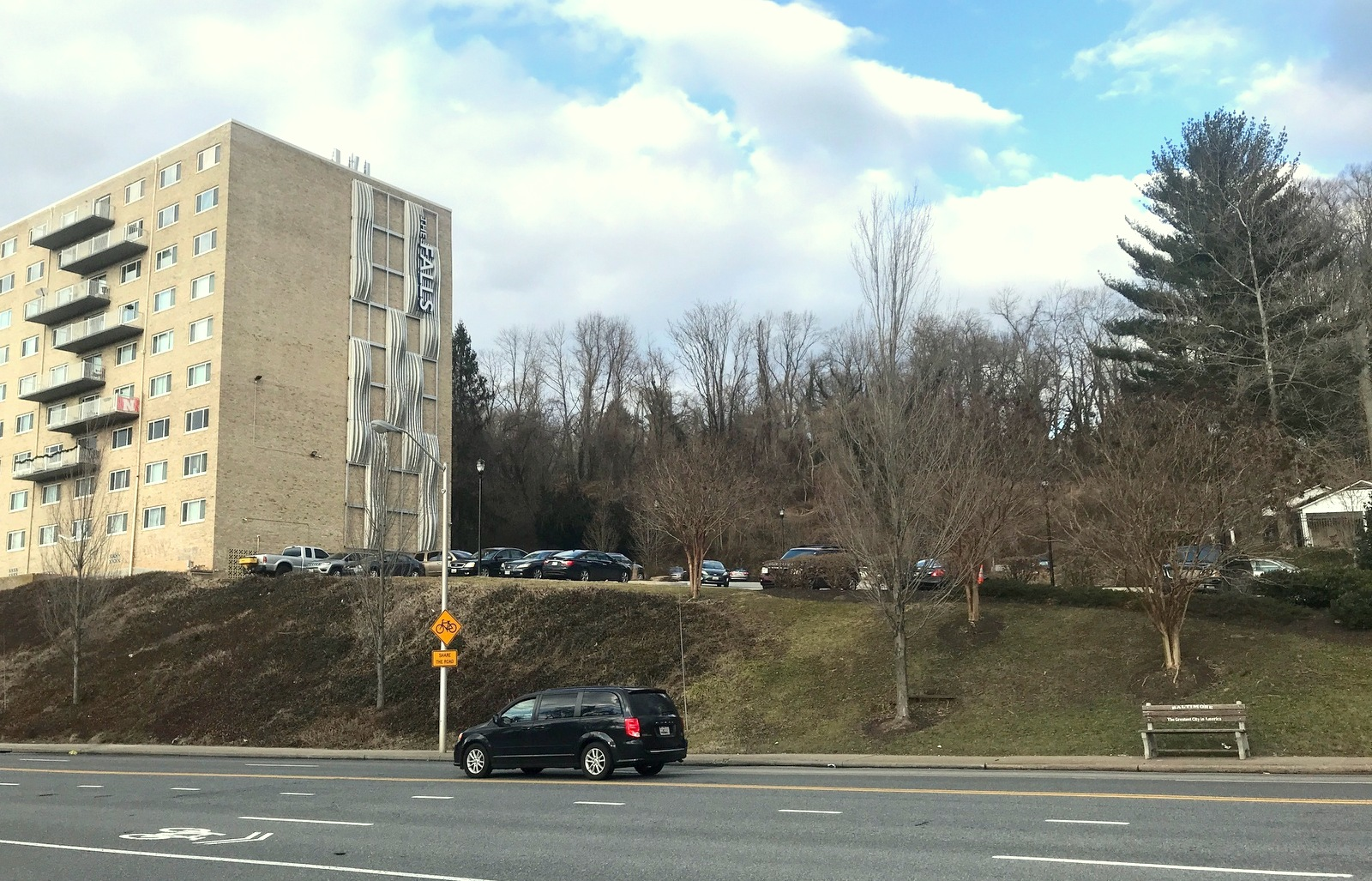 The Claiborne site would be located on the wooded hill above the Falls of Roland Park apartment building recently sold by Blue Ocean. In the foreground is Falls Road just north of Northern Parkway. (Mark Reutter)