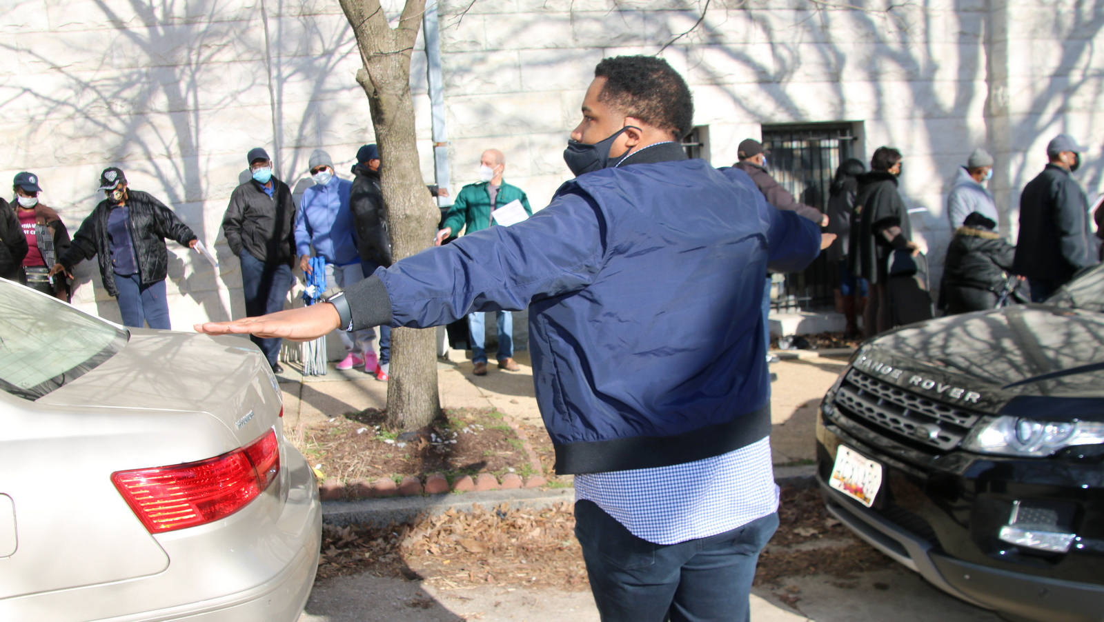 An organizer reminds people lined up to be vaccinated outside the Masonic Temple on Eutaw Place to maintain six-foot social distance. (Fern Shen)