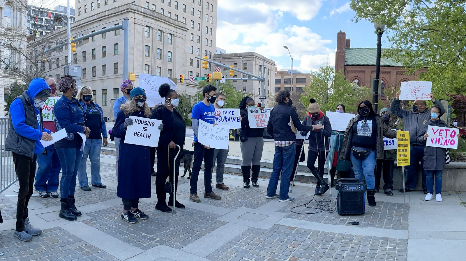 A protest organized by the Baltimore Renters United Coalition calls for Mayor Scott to veto a bill promoting surety bonds that Council President Mosby has been backing. (Fern Shen)