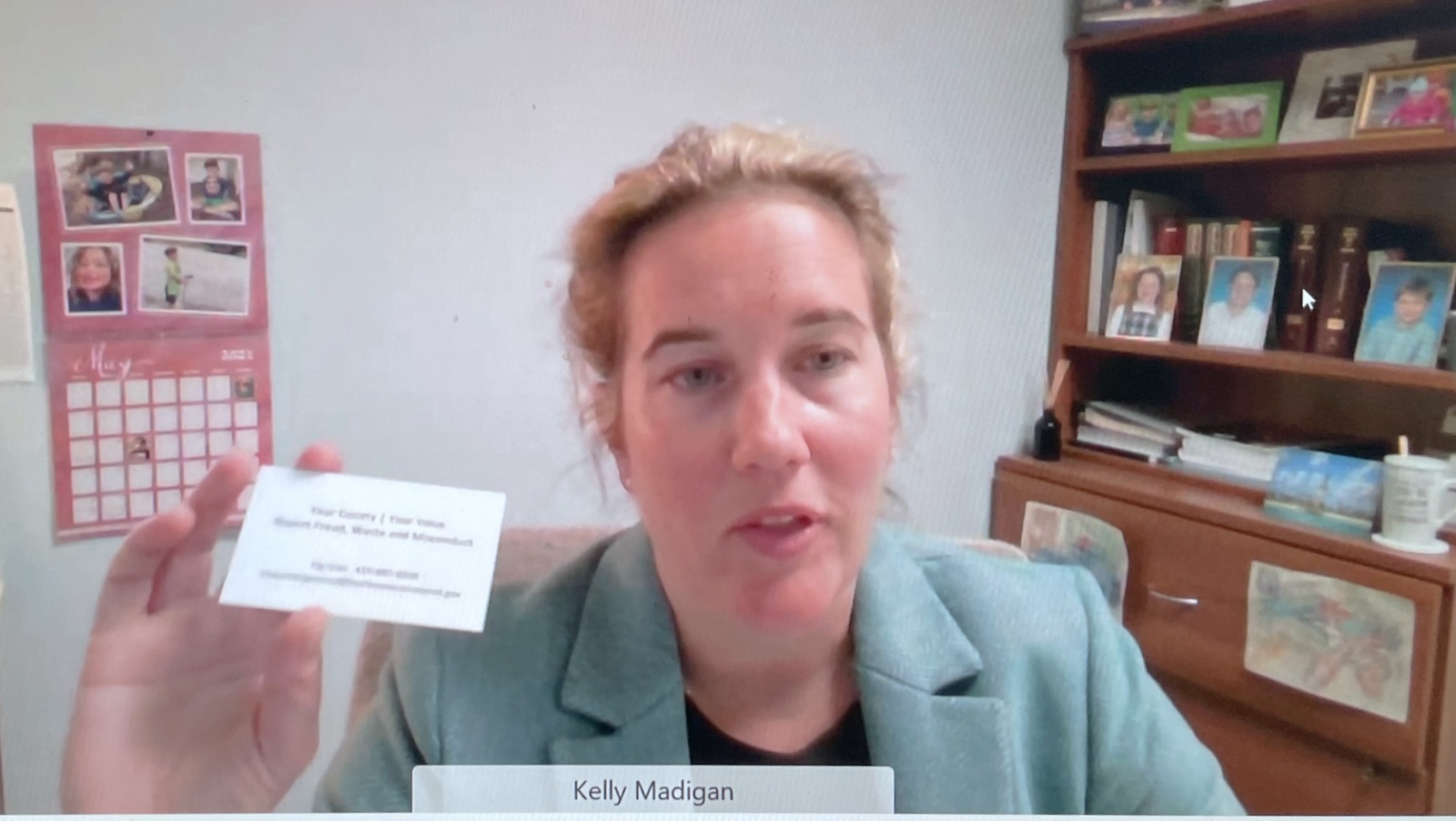 Baltimore County Inspector General Kelly Madigan holds her business card up so that meeting participants can see it, after Councilwoman Bevans demands that she do so. (WebX)