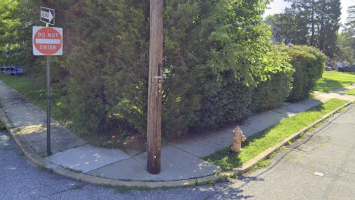 No curb ramp - and a telephone pole blocking the sidewalk - make this spot in northeast Baltimore especially non-ADA-compliant. (Google/dralegal.org)
