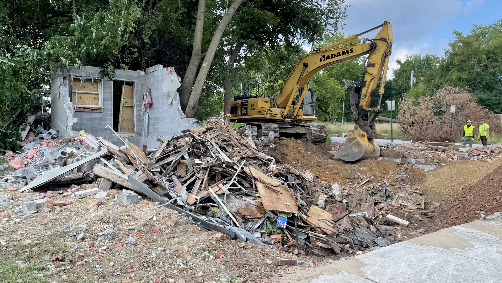 A city demolition contractor's crew pauses, after knocking down three houses at the corner of Saratoga and Arlington streets. (Fern Shen)
