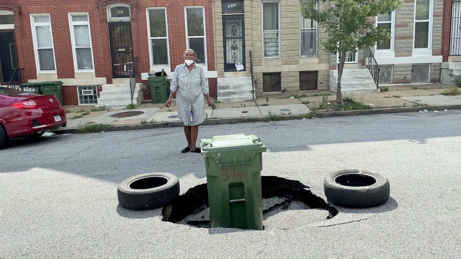 A resident points out the large hole that opened up in Carrollton Street, where trucks carrying demolition rubble were driving. (Fern Shen)