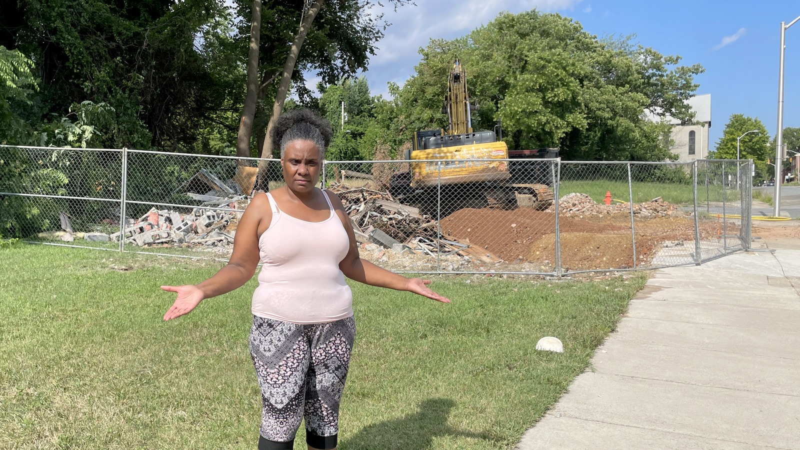 Sonia Eaddy stands in front of the historic house on her block in West Baltimore, moments after the city knocked it down. (Fern Shen)