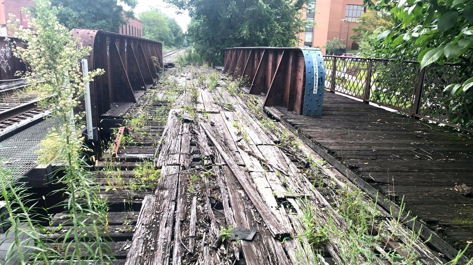 The CSX bridge over North Avenue is still used by freight trains, though one of the two tracks is abandoned. A Coppin State dorm building is seen at upper right. (Mark Reutter)