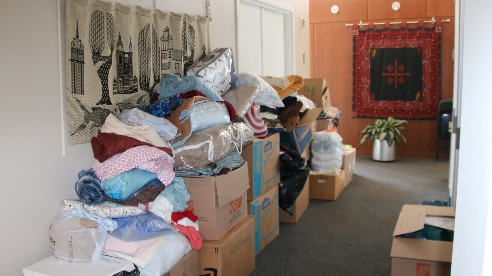 Donated bedding lines a hallway at Lutheran Immigration and Refugee Service headquarters in Baltimore. (Fern Shen)