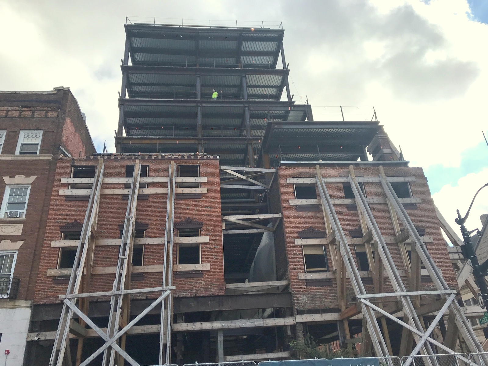 Wood beams hold up the brick facade of 1001-03 North Charles Street, while Landmark Partner's new steel tower looms above. (Mark Reutter)
